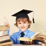 Little smiling boy in academic hat quoted old book Royalty Free Stock Image
