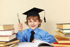 Little smiling boy in academic hat with rarity pen among old books. Little smiling boy in academic hat with rarity pen among the old books Royalty Free Stock Photography