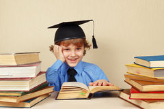 Little smiling boy in academic hat studies old books Royalty Free Stock Photo