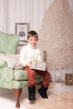 Little smiling boy on chair with present in Christmas interior Royalty Free Stock Image
