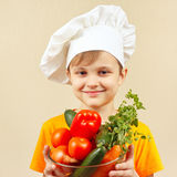 Little smiling boy in chefs hat with fresh vegetables Royalty Free Stock Photos