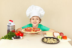 Little smiling boy in chefs hat preparing pizza Royalty Free Stock Photos