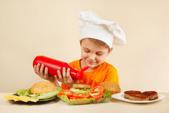 Little smiling boy in chefs hat puts sauce on hamburger Royalty Free Stock Images