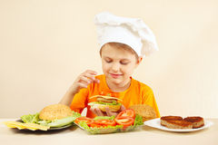 Little smiling boy in chefs hat puts tomato on hamburger Stock Photos
