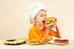 Little smiling boy in chefs hat is tasting cooked hamburger Stock Images