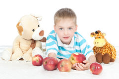 Little smiling boy eating apple on white Royalty Free Stock Images