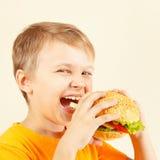 Little smiling boy eating tasty hamburger Royalty Free Stock Image