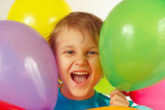 Little smiling boy between festive balls Stock Image