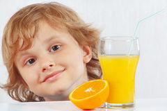 Little smiling boy with a glass of fresh juice and orange Stock Images