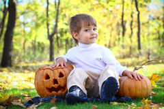 Little smiling boy with halloween pumpkins Royalty Free Stock Photos