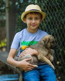Little smiling boy in a hat staying with striped cat on his hands closeup stock photo