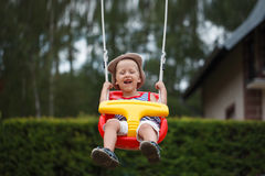 Little smiling  boy having fun and swinging on outdoor playgroun Stock Photography