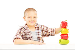 Little smiling boy holding colorful peppers on a table Stock Photo