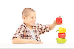 Little smiling boy holding colorful peppers on a table Stock Photography