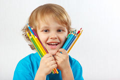 Little smiling boy holds color pencils Royalty Free Stock Photography