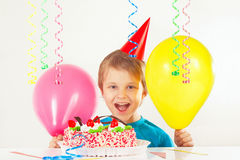 Little smiling boy in holiday cap with birthday cake and balloons Stock Image
