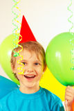 Little smiling boy in holiday hat with festive balls and streamer Stock Photo