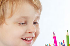 Little smiling boy looks on color pencils Stock Photos