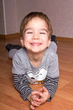 Little smiling boy is lying on a floor at home. Stock Image