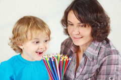 Little smiling boy with mother with color pencils Stock Image