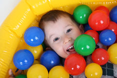 Little smiling boy playing in colorful balls playground Royalty Free Stock Images