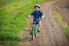 Little smiling boy ride on bike on rural landscape Stock Image