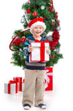 Little smiling boy in Santa hat holding present. Royalty Free Stock Images