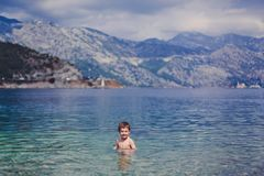 Little smiling boy in the sea with blue and turquoise water. In the background blue mountains. On a Sunny summer day. royalty free stock image