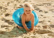 Little smiling boy sits in lifebuoy on beach. Little smiling boy sits in lifebuoy on bright sandy beach Royalty Free Stock Photography