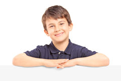 Little smiling boy standing behind a blank panel Royalty Free Stock Image