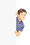 Little smiling boy standing behind a blank panel and looking at Stock Photo