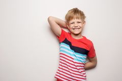 Little smiling boy in t-shirt isolated on white background. Studio portrait. Fashion stock photo