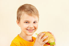 Little smiling boy with tasty hamburger Royalty Free Stock Images