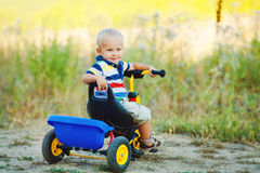 Little smiling boy on toy bicycle Stock Photography