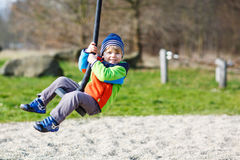 Little smiling boy of two years having fun on swing on cold day. Outdoors Stock Photos