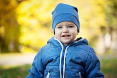 Little smiling boy on the yellow background in the sunny autumn Stock Photos