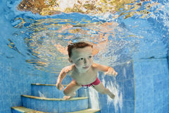 Little smiling child swimming underwater in pool Stock Photos