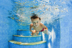 Little smiling child swimming underwater in pool Stock Image