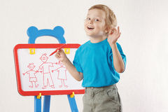 Little smiling cute boy drew family on whiteboard Royalty Free Stock Photography