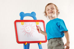 Little smiling cute boy drew a sun on whiteboard Stock Photo