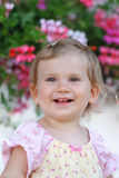 Little smiling girl. Portrait with flowers background Stock Photo