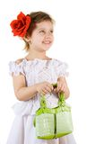 Little smiling girl. With green bag and red rouses in the hair Royalty Free Stock Photo