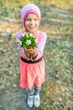 Little smiling girl with anemone nemorosa Royalty Free Stock Photo