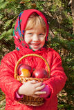 Little smiling girl with apples in a basket Stock Image