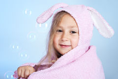 Little smiling girl after bath on blue background Stock Images