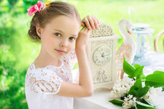 Little smiling girl with big clock. People, time management and Stock Images