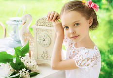 Little smiling girl with big clock. People, time management and Stock Image
