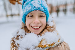 Little smiling girl in blue cap in snow Stock Photo