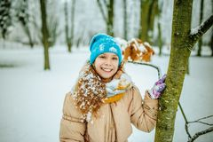 Little smiling girl in blue cap in snow Royalty Free Stock Photo