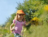 A little smiling girl with a bouquet of field summer flowers running along the path of a forest Royalty Free Stock Photography